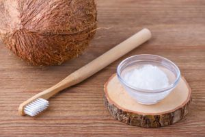 Coconut, a toothbrush, and a bowl with melted coconut oil on a wood table